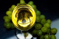 Бокал вина, виноградины, вино, пропуская от бутылки, черная предпосылка Стоковые Изображения RF