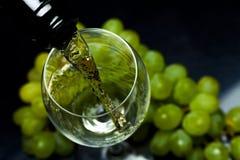 Бокал вина, виноградины, вино, пропуская от бутылки, черная предпосылка Стоковые Фото