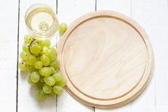 Бокал вина и виноградины с пустой разделочной доской Стоковое Фото