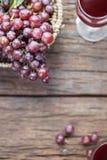 Бокал вина или сок и плодоовощ виноградины на деревянном столе Стоковое Изображение RF