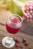 Бокал вина или сок и плодоовощ виноградины на деревянном столе Стоковые Изображения