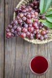 Бокал вина или сок и плодоовощ виноградины на деревянном столе Стоковые Фотографии RF