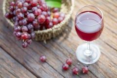 Бокал вина или сок и плодоовощ виноградины на деревянном столе Стоковое фото RF