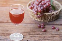 Бокал вина или сок и плодоовощ виноградины на деревянном столе Стоковое Фото