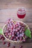 Бокал вина или сок и плодоовощ виноградины на деревянном столе Стоковая Фотография