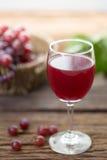 Бокал вина или сок и плодоовощ виноградины на деревянном столе Стоковые Изображения RF