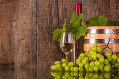 Бокал вина при бутылка бочонка белая спрятанная grapeleaves Стоковое Изображение RF