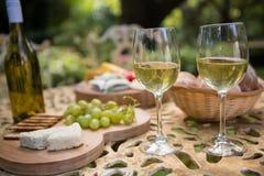 Бокал вина с сыром и виноградинами на таблице Стоковые Изображения RF