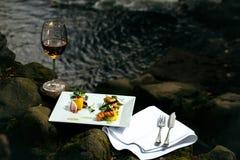 Бокал и еда около воды Стоковые Фото