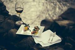 Бокал и еда около воды Стоковые Изображения RF