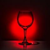Бокал красивого силуэта пустой на красном и черном backgroun Стоковая Фотография
