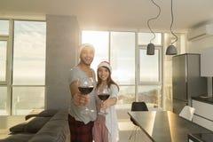 Бокалов владением пар праздника рождества квартира счастливых современная с панорамным окном вида на море Стоковая Фотография