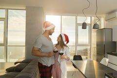 Бокалов владением пар праздника рождества квартира счастливых современная с панорамным окном вида на море Стоковая Фотография RF