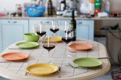 Бокалы, бутылка вина и пустые плиты на таблице Стоковая Фотография