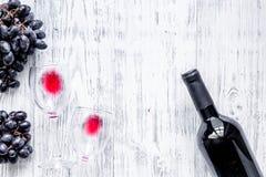 Бокалы и бутылка на светлом copyspace взгляд сверху предпосылки деревянного стола Стоковое Изображение
