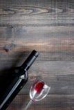 Бокалы и бутылка на темном copyspace взгляд сверху предпосылки деревянного стола Стоковые Фотографии RF