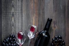 Бокалы и бутылка на темном copyspace взгляд сверху предпосылки деревянного стола Стоковое фото RF