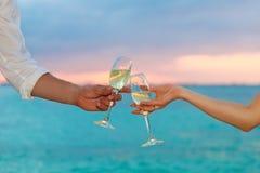Бокалы человека и женщины лязгая с шампанским на заходе солнца Стоковые Изображения RF