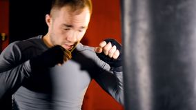 Боксер бросает тяжелые пунши на сумке бокса акции видеоматериалы