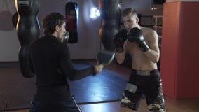 Боксер в кольце выполняет профессиональное дуновение Тренер помогает его палате для того чтобы положить в коробку, использует лап акции видеоматериалы
