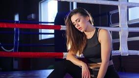 Боксер девушки дышит тяжело после тренировки