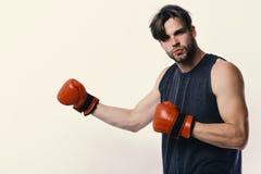 Боксер делает удары и пунши как тренировка Человек с щетинкой и серьезной стороной носит перчатки бокса Бокс и спорт Стоковое Изображение RF