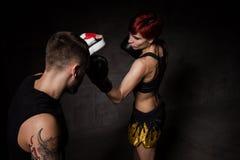 Боксер женщины ударяя перчатки тренировки держал тренера бокса стоковое фото