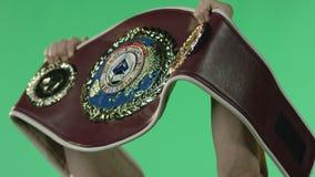 Боксер поднимает пояс чемпионата Боксер с поясом Пояс титула чемпиона мира на зеленой предпосылке акции видеоматериалы
