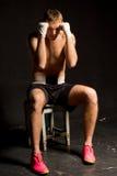 Боксер сидя на табуретке при его поднятые кулаки стоковые изображения