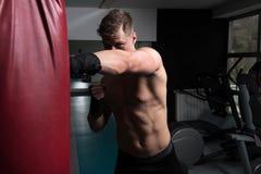 Боксер с сумкой пунша в действии Стоковое Изображение