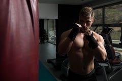 Боксер с сумкой пунша в действии Стоковые Фото