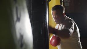 Боксер ударяет грушу Человек спорт бьет грушу Человек в спортзале Тренер играет спорт Пробивая мешок видеоматериал