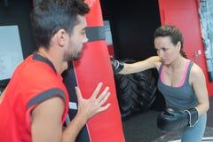 Бокс женщины в спортзале с тренером Стоковые Фото