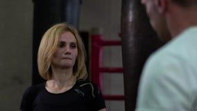 Бокс и тренировка женщины с тренером в спортзале около punchbag сток-видео