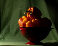 Болгарские перцы освещенные стороной в красном дуршлаге Стоковые Фотографии RF