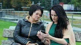 Более молодое поколение объясняет к старейшине как использовать современные устройства 2 брюнет различных времен сидят на a акции видеоматериалы