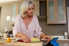Более старая женщина в кухне ища для рецепта на цифровой таблетке Стоковые Фотографии RF