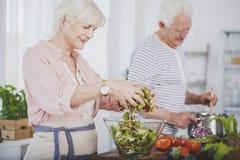 Более старая женщина меча салат стоковое фото