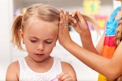 Более старая маленькая девочка помощи сестры связывает ее волосы в косичках Стоковая Фотография