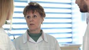 Более старая медсестра имея переговор с более молодыми коллегами стоковое изображение rf