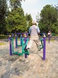 Более старый человек разрабатывая на общественном оборудовании в парке стоковые изображения rf
