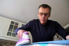Более старый человек уча как проутюжить одежды Стоковые Изображения