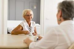 2 более старых женщины выпивая coffe дома и говорить Стоковое Изображение