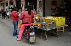 Болезненное Jia, Китай: Померанцы женщины покупая стоковое фото