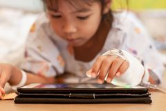 Больная азиатская девушка маленького ребенка которое имеет перевязанное решение IV играющ цифровой планшет для того чтобы ослабит стоковая фотография