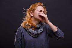 Больная девушка в сером шарфе чихает против черной предпосылки стоковое фото rf
