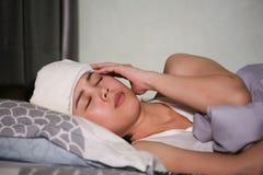 Больная женщина имея головную боль с одеялом лежа в кровати стоковая фотография rf