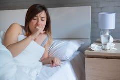 Больная женщина кашляя пока лежащ в кровати стоковые фото