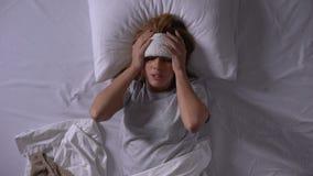 Больная женщина кладя обжатие на лоб для того чтобы принести вниз температуру и головную боль акции видеоматериалы