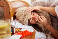 Больная молодая женщина на кровати в комнате Стоковые Изображения